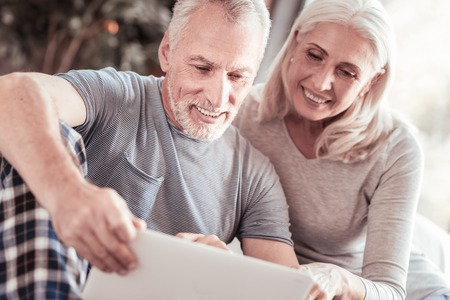 Photo for Expressing interest. Close up of positive elderly couple looking at the laptop screen while sitting together and smiling - Royalty Free Image