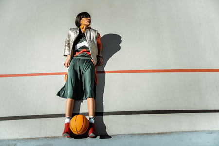 Foto de Adorable skinny girl staying against the wall with ball between her legs in warm outfit - Imagen libre de derechos