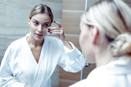 Foto de Beaming blonde-haired woman wearing white bathrobe cleaning her skin before sleep - Imagen libre de derechos
