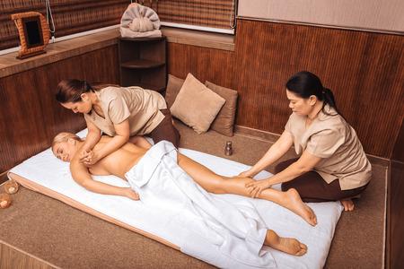 Photo pour Small pleasures. Nice good looking woman having a massage while visiting a spa center - image libre de droit