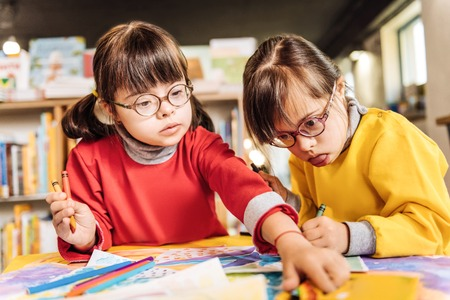 Foto de Helpful sisters. Cute appealing sisters having Down syndrome helping each other coloring pictures - Imagen libre de derechos