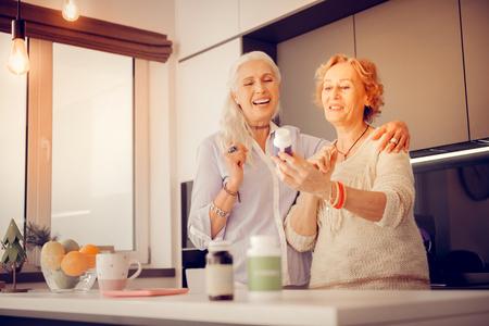 Foto de You should try. Joyful age woman holding a bottle with medicine while recommending it to her friend - Imagen libre de derechos