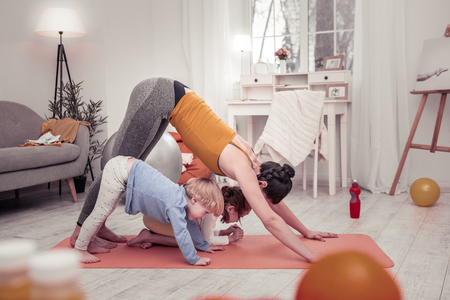 Photo for Family exercises. The mother and children doing yoga exercises every morning together - Royalty Free Image