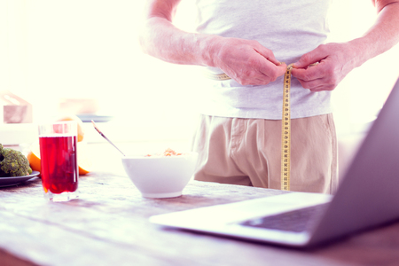 Photo pour Measuring waistline. Modern mature man working on improvement of his body measuring waistline in the morning - image libre de droit