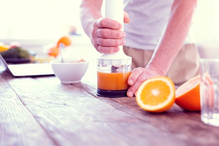 Foto per Morning juice. Close up of man using his modern blender while squeezing morning orange juice for healthy breakfast - Immagine Royalty Free
