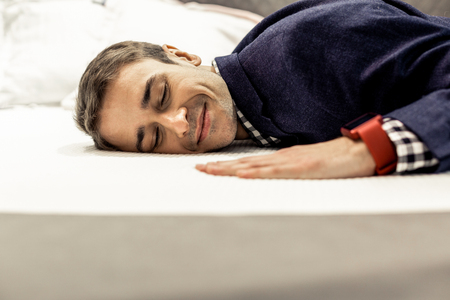 Photo pour Man lying on bed. Portrait of serene smiling mature brown-haired man wearing navy jacket with eyes closed happily lying on bed - image libre de droit