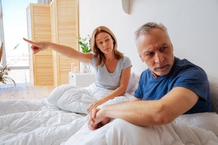Foto de Categorical wife. Grey-haired husband not listening to his categorical emotional wife - Imagen libre de derechos