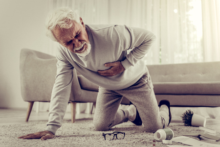 Foto de Suffering from severe heartache. Aged sick white-haired seventy-year mister suffering from severe heartache and falling down because of it - Imagen libre de derechos