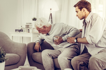 Foto de Helping person with a heart attack. Shocked adult brown-haired son trying to help his elderly grey-haired father with a heart attack. - Imagen libre de derechos