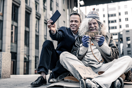 Photo pour Excited old homeless. Vain rich man in costume making selfie of donation money to desperate poor man - image libre de droit