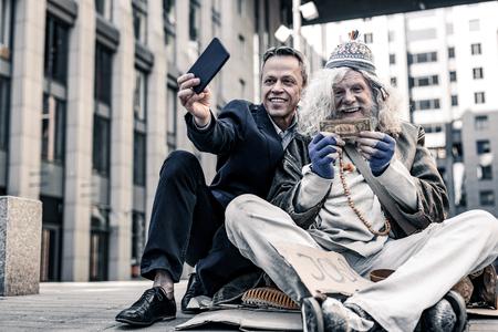 Foto de Excited old homeless. Vain rich man in costume making selfie of donation money to desperate poor man - Imagen libre de derechos