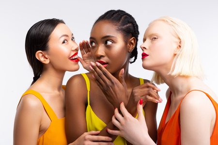 Photo for Women gossiping. Funny good-looking women with different skin gossiping about their lives - Royalty Free Image