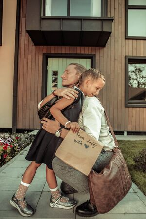 Foto de Saying goodbye to father. Caring positive dad tightly hugging young daughter before school day while staying in front of the house - Imagen libre de derechos