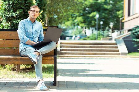 Foto de Stylish freelancer. Handsome stylish freelancer wearing glasses sitting on the bench with laptop - Imagen libre de derechos