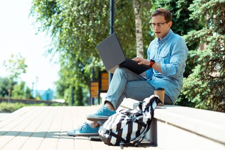 Foto de Busy freelancer. Busy freelancer working on laptop while sitting in the park near his backpack - Imagen libre de derechos