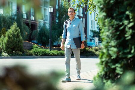 Foto de Laptop in hands. Stylish businessman wearing smart watch walking to office with laptop in hands - Imagen libre de derechos