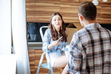 Photo for Wearing stylish earrings. Appealing young wife wearing stylish earrings eating noodles and talking to husband - Royalty Free Image