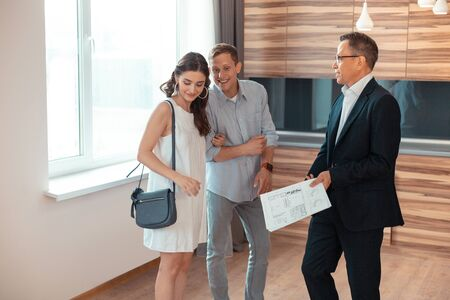 Photo for Businessmen and Real estate agent. Couple of young businessmen standing near Real estate agent showing them the house - Royalty Free Image