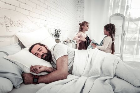 Foto de Sleeping dad with his two kids in background about to wake him up on a good day - Imagen libre de derechos