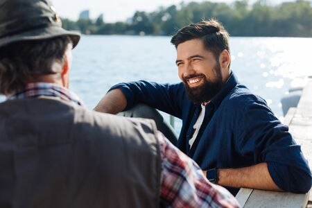 Photo pour Morning with father. Beaming bearded man feeling happy spending morning with father near lake - image libre de droit