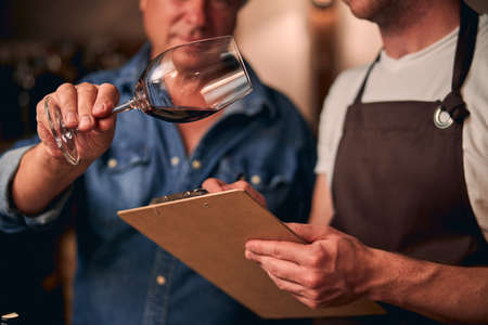 Foto de Two unrecognized sommeliers in a winery making notes on a clipboard while evaluating red wine in a glass - Imagen libre de derechos