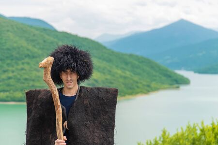 Photo for Georgian man in a beech costume on a background of mountains. Selective focus. - Royalty Free Image
