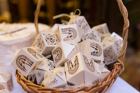Photo for White boxes for guest attending the wedding in the basket. Shaped favors the house that contain confetti. Bonbonniere for guests. - Royalty Free Image