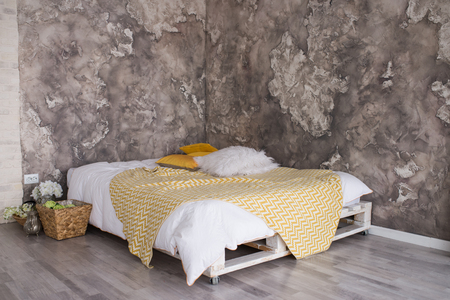 Foto de A loft style bedroom with recycled pallet bed. White and yellow bedding on bed with bedhead in loft - Imagen libre de derechos
