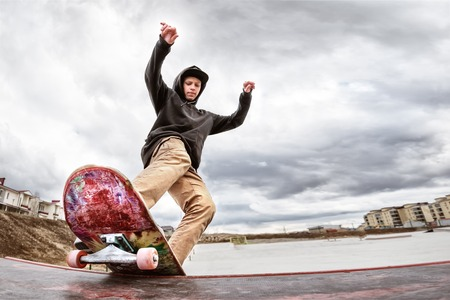 Photo pour Teen skater in a hoodie sweatshirt and jeans slides over a railing on a skateboard in a skate park - image libre de droit