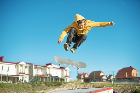Photo pour A teenager skateboarder does an flip trick in a skatepark on the outskirts of the city - image libre de droit