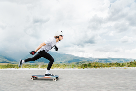 Foto de The young Longboarder pushes his foot out on his longboard over the country road - Imagen libre de derechos