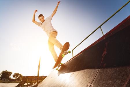 Photo pour Teen skater hang up over a ramp on a skateboard in a skate park - image libre de droit