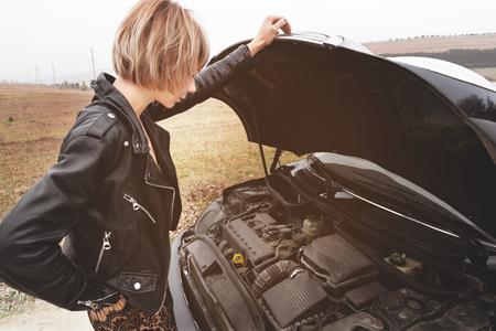 Foto de Girl opening the hood of her car checks the engine oil level - Imagen libre de derechos