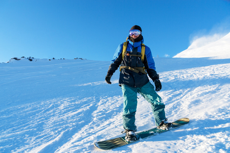 Foto de Freeride snowboarder rolls on a snow-covered slope leaving behind a snow powder against the blue sky - Imagen libre de derechos