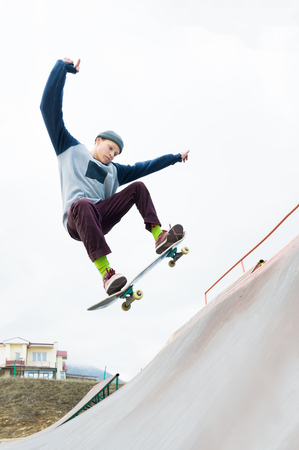 Photo pour A skateboarder teenager in a hat does a trick with a jump on the ramp. A skateboarder is flying in the air - image libre de droit