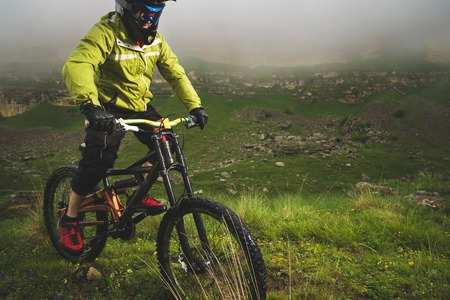 A man in a mountain helmet riding a mountain bike rides around the beautiful nature in cloudy weather. downhill