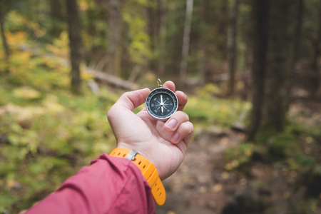 Photo pour A beautiful male hand with a yellow watch strap holds a magnetic compass in the coniferous autumn forest. The concept of finding yourself the way and truth - image libre de droit