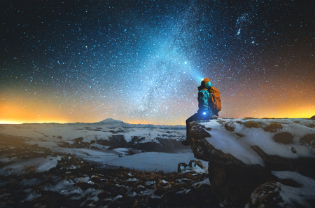Foto de Night winter landscape a man with a backpack and a lantern on his head sits on a rock in the mountains in winter against the background of a mountain and a winter starry sky and the Milky Way - Imagen libre de derechos