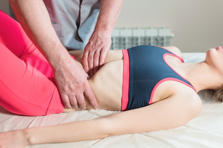 Photo pour Male manual visceral therapist masseur treats a young female patient. Edit the internal organs and the elimination of adhesions in the stomach - image libre de droit