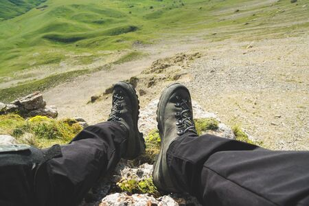 Photo for A first-person view POV of a man sits on the edge of a high cliff and enjoys the scenery. Wide angle human foot trekking rest. Tourism concept - Royalty Free Image