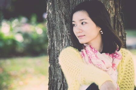Portrait of happy looking woman sitting against a tree and looking to the side