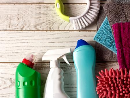 Foto de Colored microfiber napkins, cleaning agent, spray and brush on the white floor. - Imagen libre de derechos