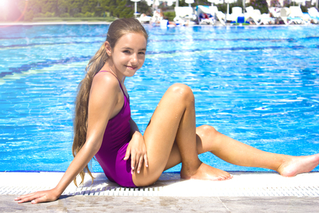 Photo pour Beautiful teenage girl in purple swimsuit sitting by the poolside and smiling to camera - image libre de droit