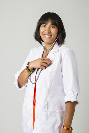 Young filipino woman wearing a lab coat and checking her health with a stethoscope