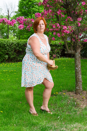 Foto de forty something brunette woman wearing a sun dress throwing a hat - Imagen libre de derechos