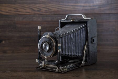 Photo for Antique medium format camera against a dark brown oak wood background - Royalty Free Image