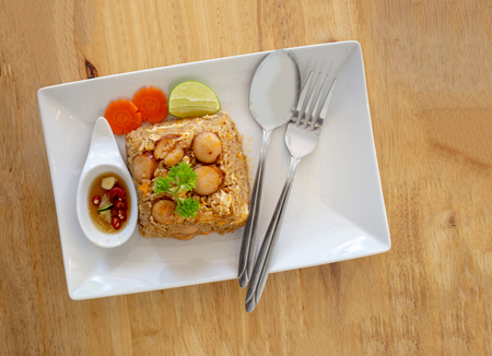 Foto de Thai food fried rice saucesage and egg serve on white ceramic plate on wood table from top view - Imagen libre de derechos