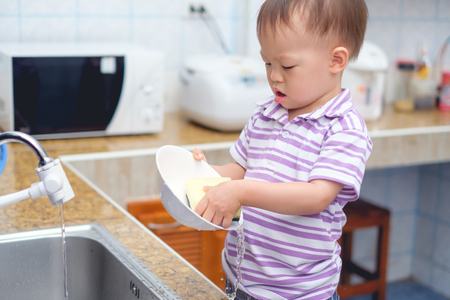 Foto de Cute little Asian 2 year old toddler boy child standing & having fun doing the dishes, concentrate on washing dishes in kitchen at home, Little home helper, chores for kids, child development concept - Imagen libre de derechos