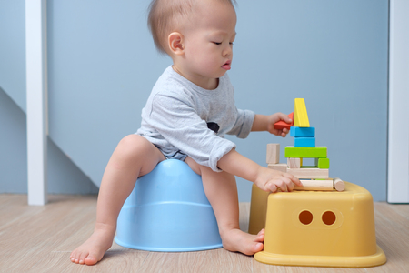 Foto de Cute little Asian 18 months old / 1 year old toddler baby boy child sitting on potty playing with wooden blocks toy. Kid playing with educational toy & Toilet training concept. - Selective focus - Imagen libre de derechos