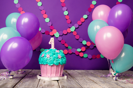 Photo pour First birthday cake with a unit on a purple background with balls and paper garland. - image libre de droit